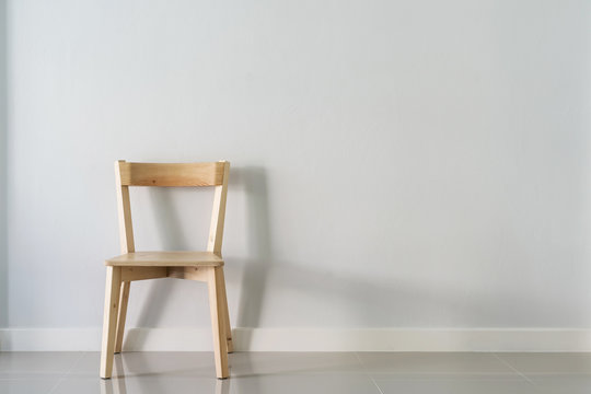 wooden chair against white wall in empty room
