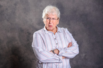gray hairy elderly woman with crossed arms looking angry