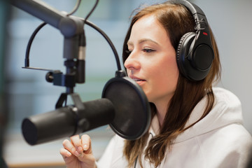 Radio Jockey Looking Away While Using Headphones And Microphone