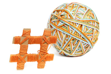 Hashtag made from cardboard and thread with big colorful thread ball isolated on white background. Cotton thread ball made from different color (orange, yellow, green, blue) with hashtag sign.