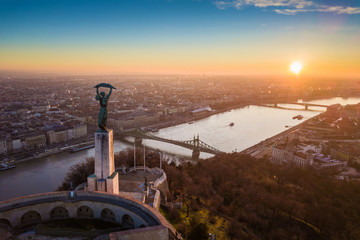 Budapest, Hungary - Aerial panoramic sunrise view at the Statue of Liberty with Liberty Bridge and River Danube at background taken from Gellert Hill