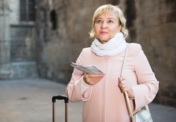 Mature woman with map and baggage