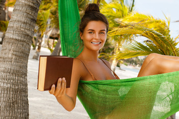 Happy and beautiful woman lying in the hammock and reading book