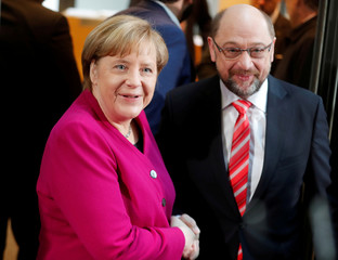 CDU leader and acting German Chancellor Merkel and SPD leader Schulz shake hands a speech before exploratory talks about forming a new coalition government at the SPD headquarters in Berlin