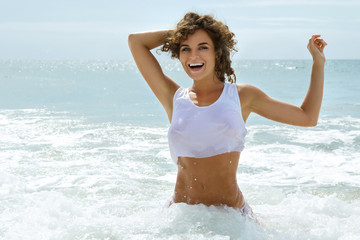Beautiful woman in a wet shirt in the sea