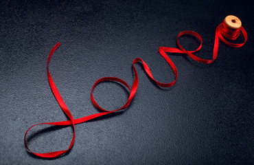 Inscription, word love of red satin ribbon.Valentine day background.Love concept.On dark stone background..Creative