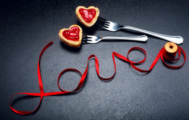 Inscription, word love of red satin ribbon and two hearts of toast bread with red jam on fork.Valentine day background.Love concept.On dark stone background.Creative.Love background.