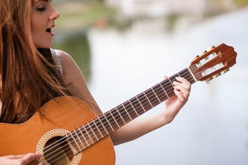 Guitar romantic city musician performance. woman playing stringed instrument and singing. Lifestyle of talented people.