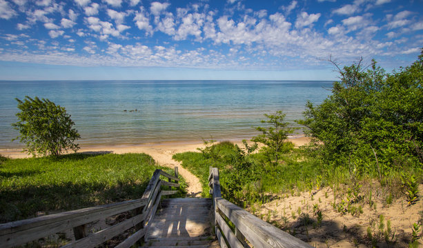 Sunny Summer Beach Background. Stairs lead to a beautiful sandy beach with crystal clear blue water and a sunny summer blue sky at the horizon. Northern shore of Lake Michigan in the Upper Peninsula.