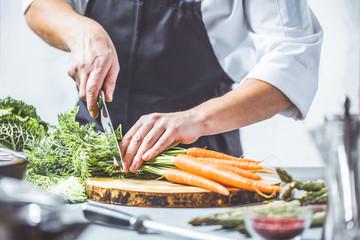 Chefkoch in der Küche mit Frischem Gemüse(Karotten)