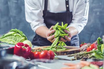 Chefkoch in der Küche mit Frischem Gemüse(Zuckererbsen)
