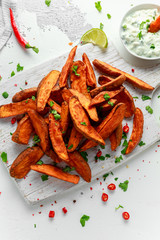 Healthy Homemade Baked Orange Sweet Potato wedges with fresh cream dip sauce, herbs, salt and pepper.