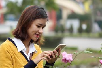 スマートフォンで花の写真を撮影する女性