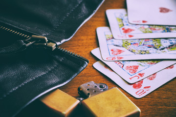 Got lucky by royal flush at poker game. Playing cards, retro leather jacket and old gasoline lighter on a wooden table. Vintage style