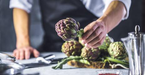 Chefkoch in der Küche mit Frischem Gemüse(Artischocken)