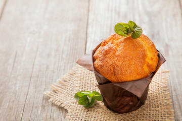 Muffins with mint on a wooden table