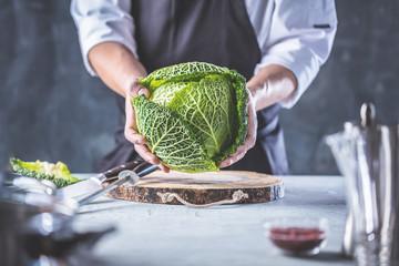 Chefkoch in der Küche mit Frischem Gemüse(Wirsing)