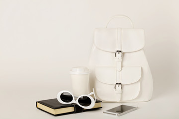 White female backpack, smartphone, notebook and sunglasses on a white background.