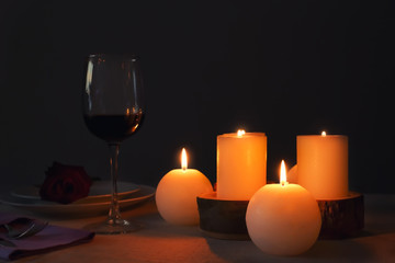 Burning candles and glass of wine on table in darkness
