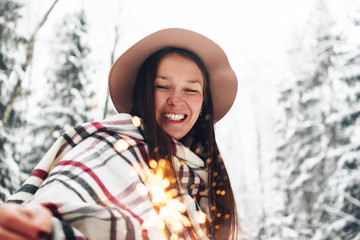 Happy and cheerful girl laughs and has fun with bengal fire in her hand. Handsome woman wearing scarf and hat walking among snowy trees in winter forest