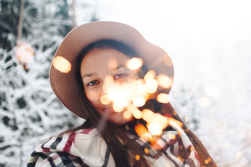 Bengal light close-up in hand beautiful woman. Pretty hipster girl have fun in winter time among snowy forest. Boho style. Wearing vintage hat, checkered scarf or poncho