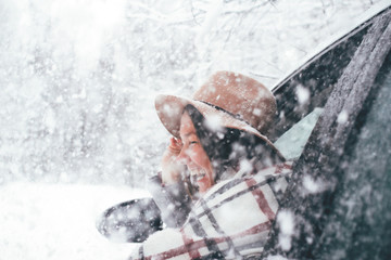 Happy woman is wearing hat and checkered scarf hanging out of the car window traveling on winter forest and enjoying heavy snowfall. Smiling hipster girl admire snowy road