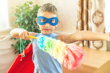 Boy child superhero costume playing is cleaning the house. Concept of children helping their parents