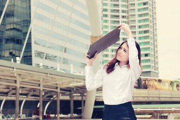 Vintage toned image of attractive business woman raises office document folder to shield from sunlight at street city.