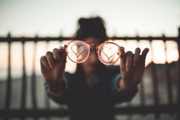 Simbolo del Cuore sugli occhiali di vetro appannato tenuti in mano da una ragazza.