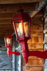 Close up of illuminated red vintage lanterns at the entrance of wooden cabin