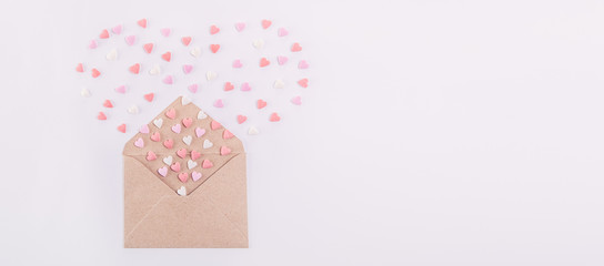 Sweets sugar candy hearts fly out in the form of heart from craft paper envelope on the white background . Valentine day concept. Gift for lover. Selective focus. Space for text. Wide banner