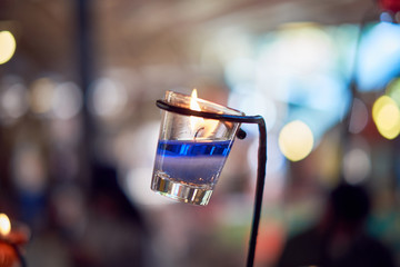 Blue candle in the glass and bokeh background. subject is blurred.