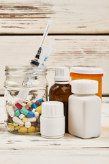 Drugs and syringes. Bottles of diverse tablets and capsules. Dangerous habits and addiction.