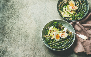 Healthy vegetarian breakfast bowls. Quinoa, kale, green beans, avocado, egg and tahini dressing bowls over grey concrete background, selective focus, copy space. Energy boosting, diet food concept
