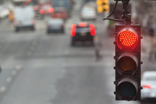 Traffic light in the city with red signal on the background of the road