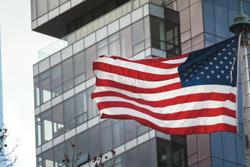 American flag on the background of the glass building