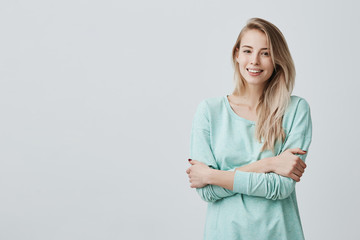 Studio shot of pretty blonde girl with perfect teeth and healthy clean skin having rest indoors, smiling happily after receiving good positive news. Beautiful young woman standing with folded arms