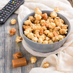 Bowl of a caramel popcorn. Homemade golden sweet corn on wooden grey table. TV remote control