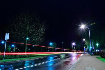 Ulica w mieście w nocy oświetlona lampami i smugi świateł samochodów.