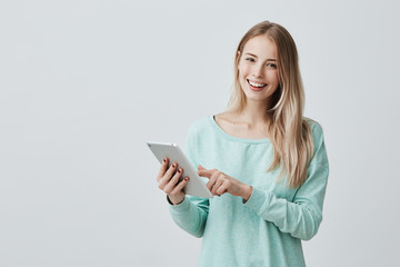 Portrait of happy young blonde business woman in casual clothes using tablet isolated against gray background. Smiling pretty girl holding a digital tablet computer. Modern technologies and business