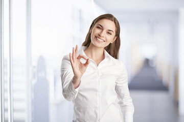 Everything is perfect at the business life. Beautiful young woman gesturing okay sign.