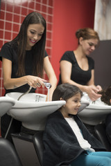 Hairdressers with little girls, cleaning head in sink