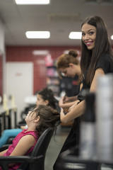 Hairdressers with little girls in beauty center saloon, woman looking at camera and smile