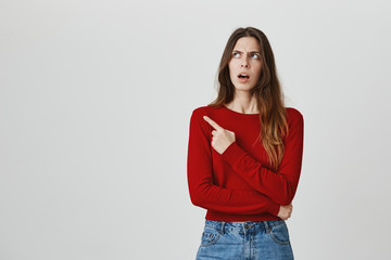 Don't listen to him. Close up portrait of young pretty caucasian female student with brown hair in red jumper and denim jeans pointing on his friend with unsatisfied face expression. Copy space
