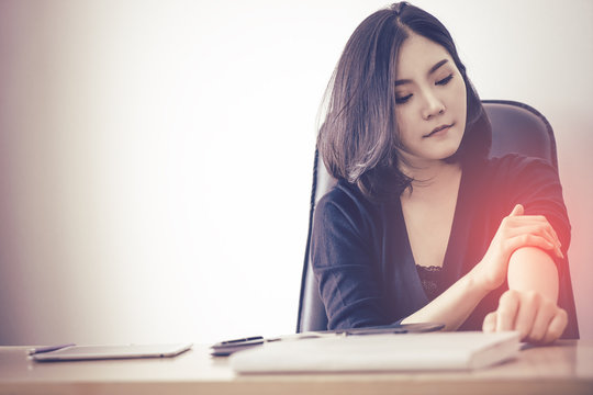 Female Asian Office worker is suffering from Office syndrome fatigue injury on her arm.