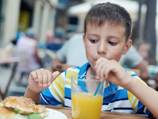 Cute boy enjoying orange juice and a burger in a street cafe.