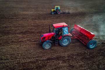 Wall Mural - Tilt shift of aerial view of tractors working on the harvest field