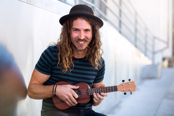 Friendly hipster man with warm personality smiling and playing a ukulele guitar