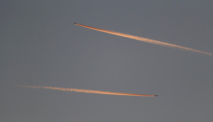 Passenger planes leave behind contrails as they fly in the skies over London Luton Airport, Luton