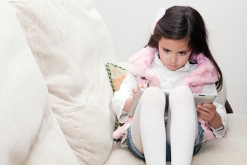 girl on the couch handles a tablet